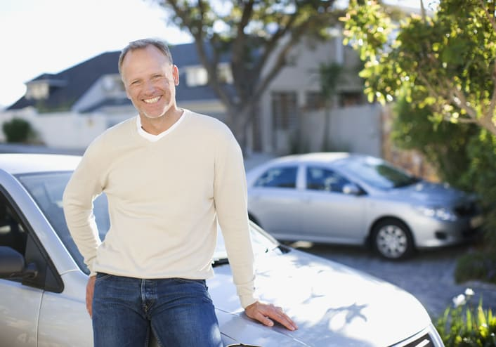 Man leaning on car hood