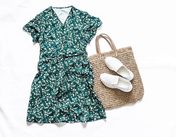 Summer women's clothing set - boho dress on the smell, straw tote bag, white leather sneakers on a light background, top view